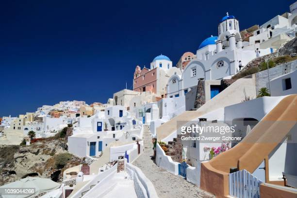 Alleys of Oia, Ia, and a domed church, with typical Cycladic architecture, Santorini, Cyclades, Greece