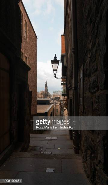 alleyway in edinburgh with scott monument on background and streetlight on foreground, scotland, united kingdom - town stock pictures, royalty-free photos & images