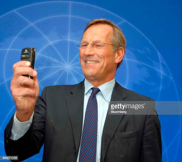 Allianz Chief Executive Michael Diekmann takes a photo with a mobile phone prior to the company's annual press conference in Munich Thursday Feb 22...