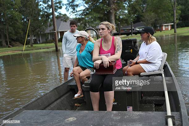 Allie Amond holds a box with her father's ashes in it that she retrieved from her flooded home on August 15, 2016 in Baton Rouge, Louisiana....