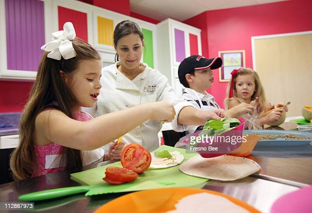Allie Foyerlicht second from left of Young Chefs International helps Kennedy SilvaCosta far left her brother Harrison center right and Britton make...