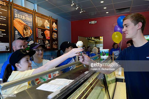 Allie Levine who has cystic fibrosis left gives a free scoop of Ben Jerry's Ice Cream to Will Thompson at the Ben Jerry's Store on 2339 East Evans...
