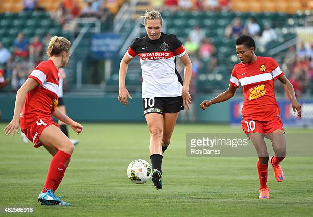 Allie Long of Portland Thorns FC passes the ball between the defense of Abigail Dahlkemper and Halimatu Ayinde of the Western New York Flash during...