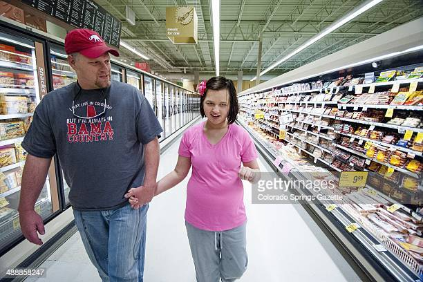 Allie Swann holds hands with her father Butch Swann as they walk through the grocery store Wednesday April 9 in Colorado Springs Colo Allie who used...