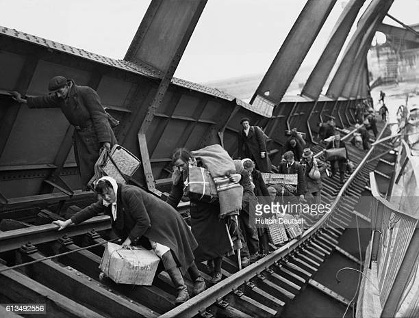Allied families laiden with belongings struggle to cross the damaged bridge at Tangemonde bombed by the Germans during World War II Germany 1945 |...