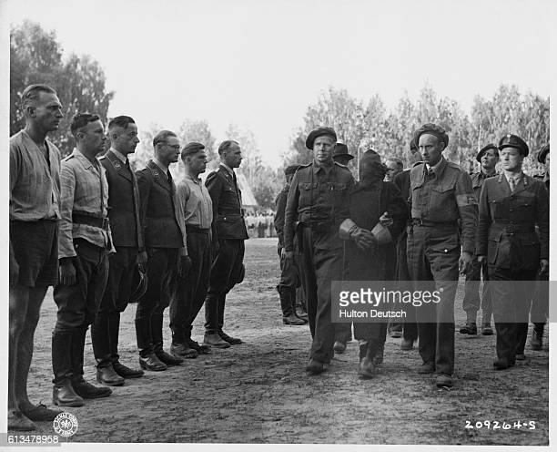 Allied intelligence personnel in Oslo Norway lead a disguised informant past a row of captured German soldiers looking for Gestapo officers hidden...