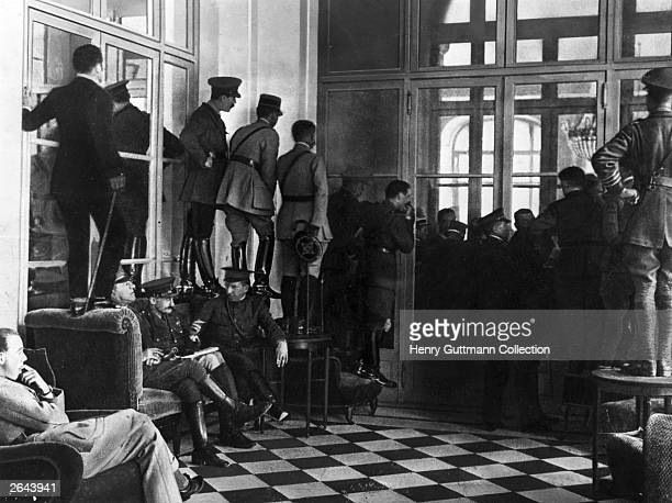 Allied officers standing on chairs and tables to see into the Hall of Mirrors where the Peace Treaty of Versailles is being signed