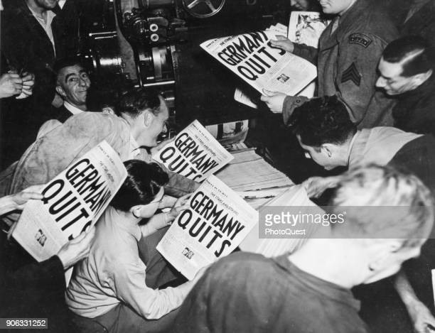 Allied soldiers and others read copies of the Stars and Stripes military newspaper off the press that announces Germany's surrender in World War II...