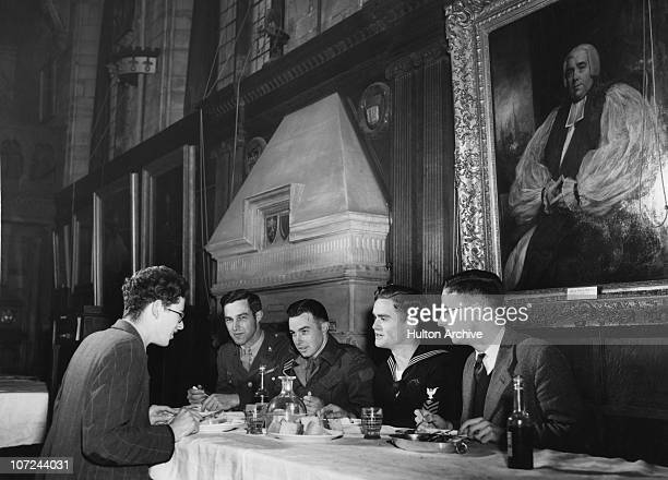 Allied soldiers and sailors eating with students in the Great Hall at Balliol College Oxford University circa 1943 From left to right undergraduate...