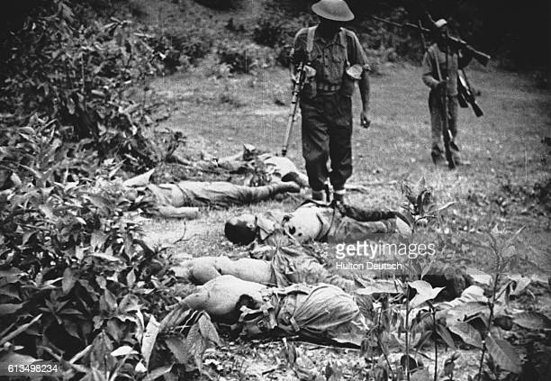 Allied soldiers walk amongst the bodies of the dead in Burma during World War II