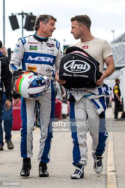 J Allmendinger and Oswaldo Negri Jr talk as they walk together in the pits during the Roar Before the 24 IMSA WeatherTech Series testing at Daytona...