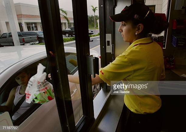Allondra Blanco hands customers their order from the drivethrough window June 8 2006 in Miami Florida In a move that significantly reduces trans...
