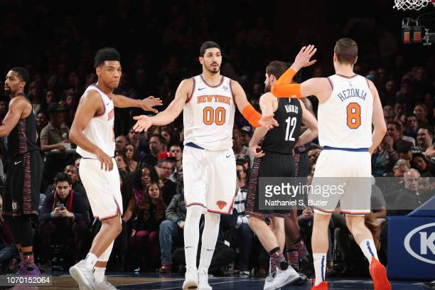 Allonzo Trier Enes Kanter and Mario Hezonja of the New York Knicks exchange high fives against the Brooklyn Nets on December 8 2018 at Madison Square...