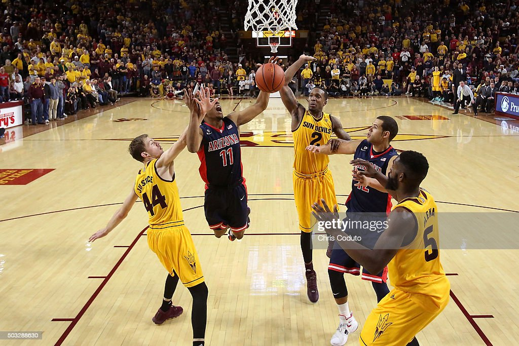 Allonzo Trier #11 of the Arizona Wildcats drives to the basket Kodi Justice #44 of the Arizona State Sun Devils (left) and Willie Atwood #2 (R) during the second half of the college basketball game at Wells Fargo Arena on January 3, 2016 in Tempe, Arizona. The Arizona Wildcats beat the Arizona State Sun Devils 94-82.