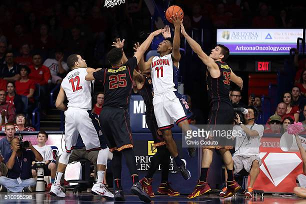 Allonzo Trier of the Arizona Wildcats shoots over Bennie Boatwright and Nikola Jovanovic of the USC Trojans during the second half of the college...