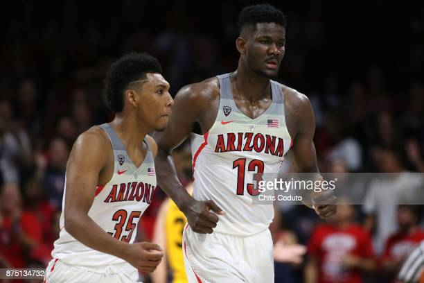 Allonzo Trier of the Arizona Wildcats walks off the floor with teammate Deandre Ayton during the second half of the college basketball game against...