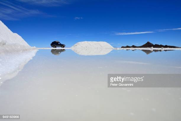 All-terrain vehicle reflected in a salt varnish, salt mining on the salt lake, Salar de Uyuni, Uyuni, Potosi, Bolivia