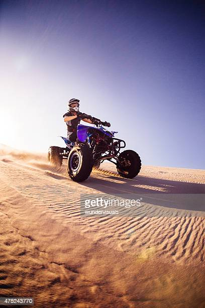 All-terrain vehicle travelling over a sand dunes