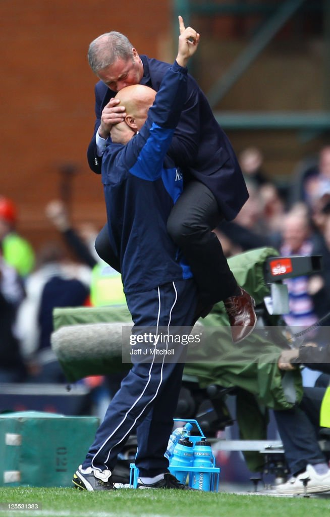 Ally McCoist coach of Rangers celebrates his teams third goal with Kenny McDowell during the Clydesdale Bank Premier League match between Rangers and Celtic at Ibrox Stadium on September 18, 2011 in Glasgow, Scotland.