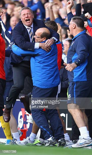 Ally McCoist coach of Rangers tackles celebrates his teams equaliser during the Clydesdale Bank Premier League match between Rangers and Celtic at...