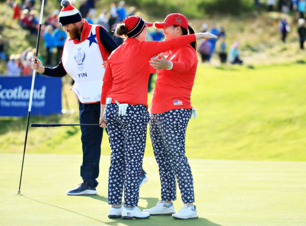 Ally McDonald and Angel Yin of Team USA hug after winning their match on the thirteenth green during Day 1 of The Solheim Cup at Gleneagles on...