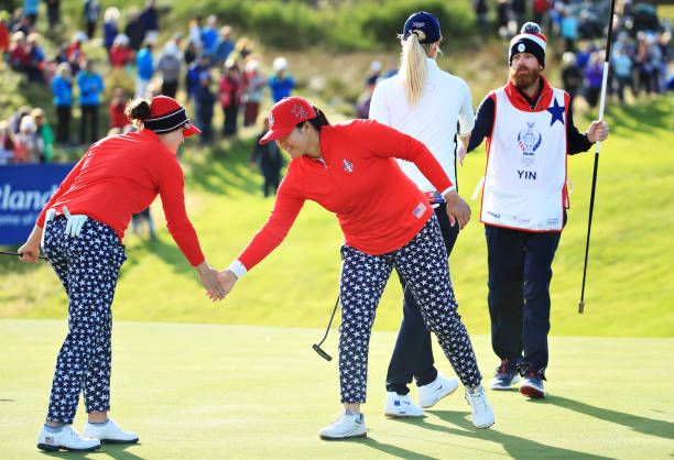 Ally McDonald and Angel Yin of Team USA shake hands after winning their match on the thirteenth green during Day 1 of The Solheim Cup at Gleneagles...