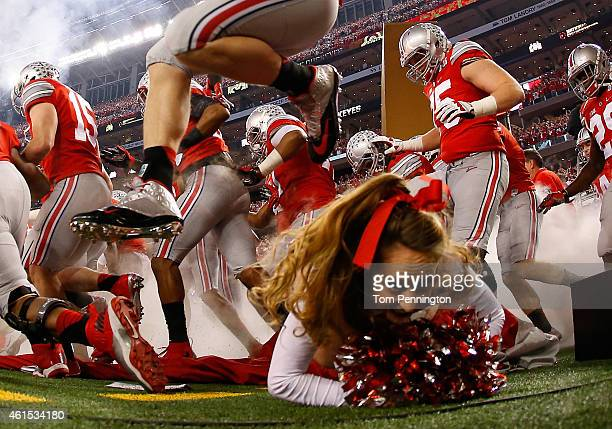 Ally Nelson an Ohio State Buckeyes cheerleader falls as the Buckeyes run out to the field before the College Football Playoff National Championship...