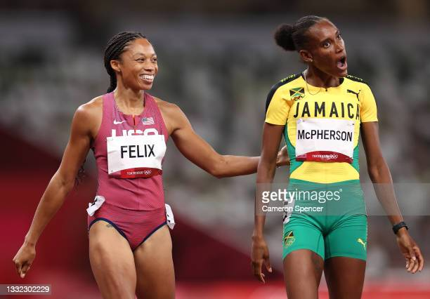 Allyson Felix of Team United States and Stephenie Ann McPherson of Team Jamaica interact after competing in the Women's 400m Semi-Final on day twelve...