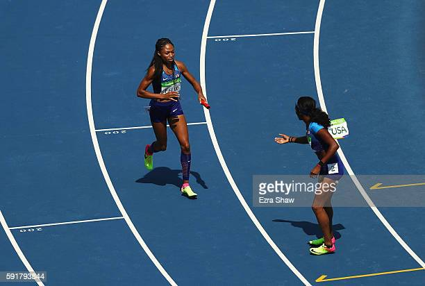 Allyson Felix of the United States picks up the baton and hands it to English Gardner after it was dropped during round one of the Women's 4 x 100m...