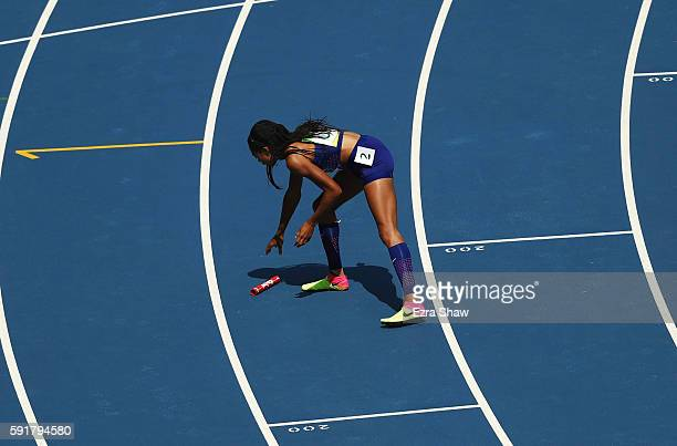 Allyson Felix of the United States picks up the baton to hand it to English Gardner after it was dropped during round one of the Women's 4 x 100m...