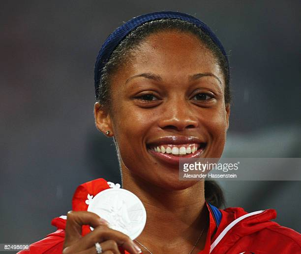 Allyson Felix of the United States receives the silver medal during the medal ceremony for the Women's 200m Final held at the National Stadium during...