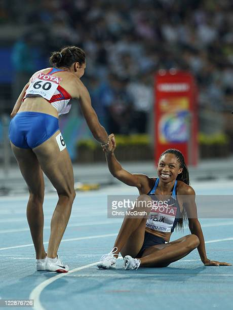 Allyson Felix of United States is helped to her feet by Anastasiya Kapachinskaya of Russia after the women's 400 metres final during day three of the...