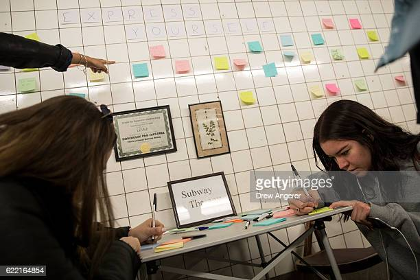 Alma Berti writes a message on a postit note as part of a public art project entitled 'Subway Therapy' at the 6th Avenue subway station November 10...