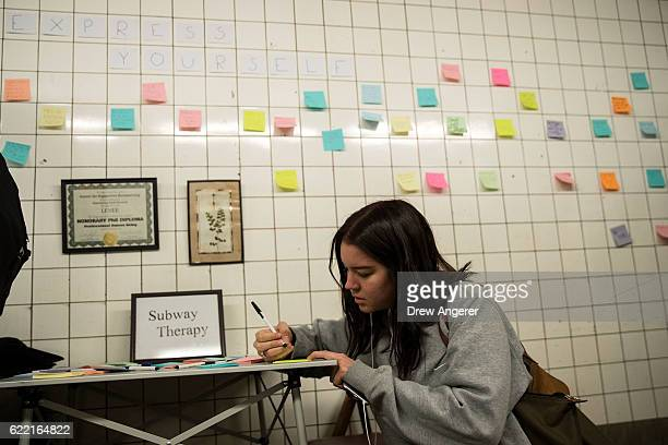 Alma Berti writes a message on a postit note as part of an art exhibit entitled 'Subway Therapy' at the 6th Avenue subway station November 10 2016 in...