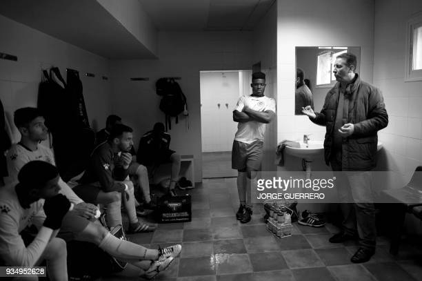 Alma de Africa Union Deportiva players listen to the coach Alejandro Benitez before their football match against Espera CF in Espera on March 18 2018...