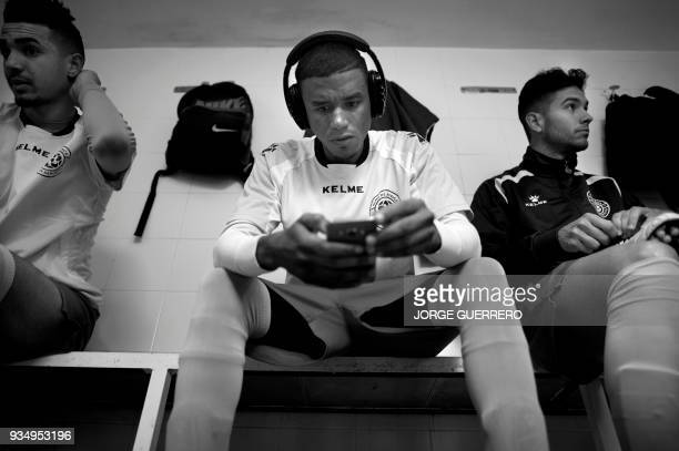 Alma de Africa Union Deportiva's Cameroonian player Karim Issa Abdou listens to music before a football match against Espera CF in Espera on March 18...