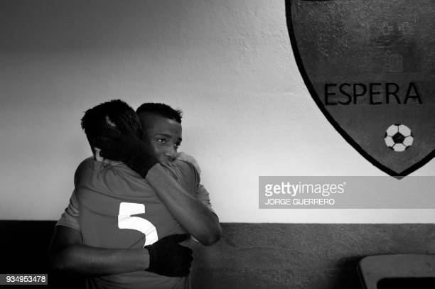 Alma de Africa Union Deportiva's forward Abdul hugs an Espera CF player after their football match in Espera on March 18 2018 / STORY 'Sporting glory...