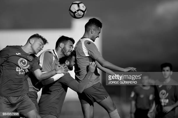 Alma de Africa Union Deportiva's midfielder Mohamed and defender Zarzuela jump for the ball during their football match against Espera CF in Espera...