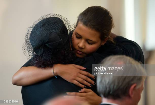 Almaz Boehm the widow of Karlheinz Boehm and her daughter Aida hug each other at the memorial service of their father and husband Karlheinz Boehm in...
