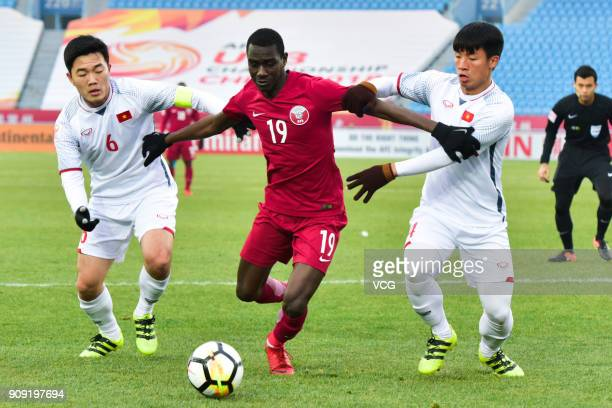Almoez Ali of Qatar and Bui Tien Dung II of Vietnam compete for the ball during the AFC U23 Championship semifinal match between Qatar and Vietnam at...