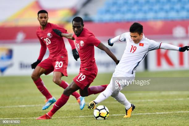 Almoez Ali of Qatar and Nguyen Quang Hai of Vietnam compete for the ball during the AFC U23 Championship semifinal match between Qatar and Vietnam at...