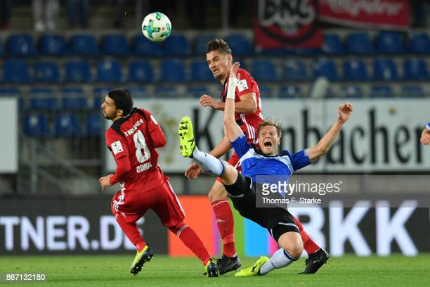 Almog Cohen and Stefan Kutschke of Ingolstadt and Brian Behrendt of Bielefeld fight for the ball during the Second Bundesliga match between DSC...