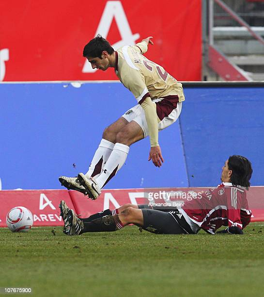Almog Cohen of Nuernberg fights for the ball with Steven Cherundolo of Hannover during the Bundesliga match between 1 FC Nuernberg and Hannover 96 at...