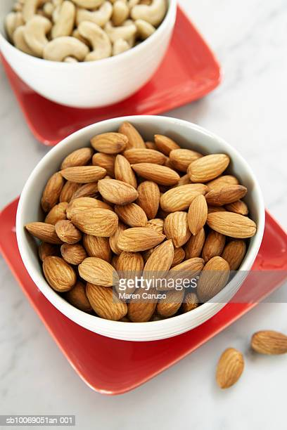 Almond and cashew nuts in bowls, close-up, elevated view