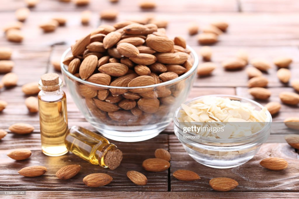 Almond and oil in bottles on brown wooden table : Stock Photo
