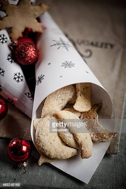 Almond cookies in paperbag with red Christmas baubles on wooden table