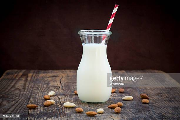 Almond milk in glass, drinking straw, on wood