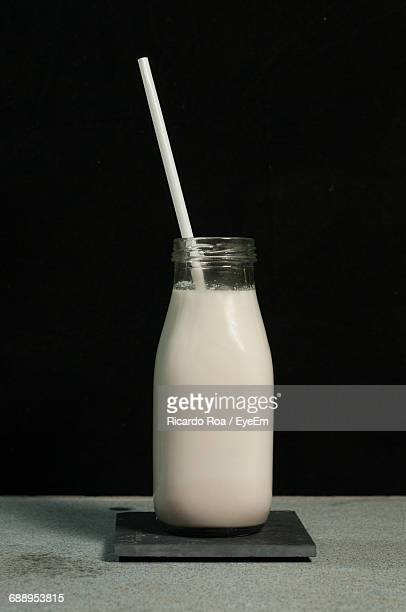 Almond Milk In Glass With Straw On Table Against Black Background