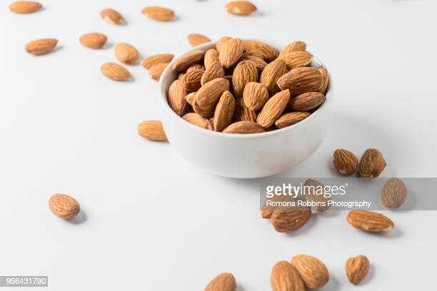 almond nuts in bowl and on white background - almond stock pictures, royalty-free photos & images
