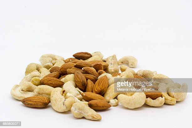 almonds and cashew nuts over white background - cashew stock pictures, royalty-free photos & images